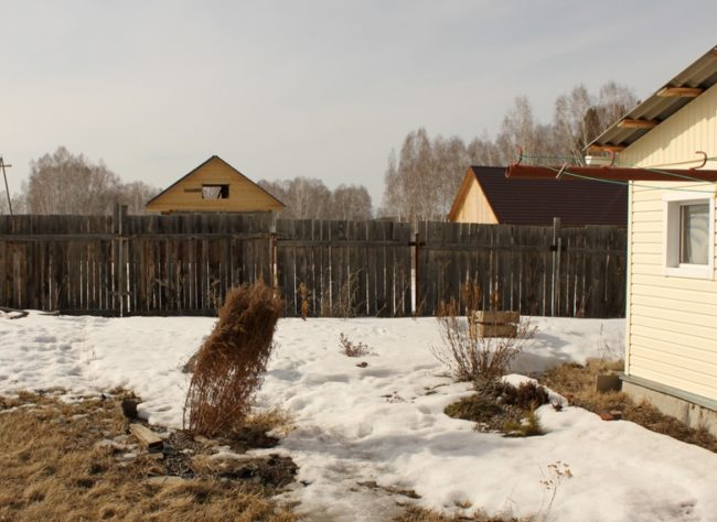 Тающий белый снег в саду