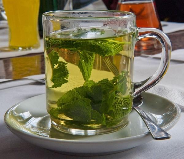 Чай из свежих листьев крыжовника в стеклянной кружке, народное тонизирующее средство