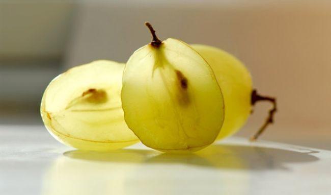 Разрезанная на две половинки ягода зеленого винограда и косточки в середине мякоти