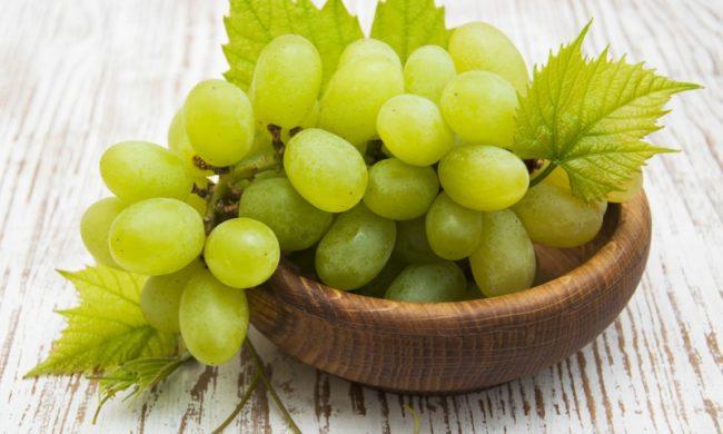 Кисть зелёного винограда с листьями в деревянной тарелке