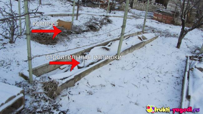 Укрытый на зиму виноград перегноем и строительнымими остатками припорошен снегом