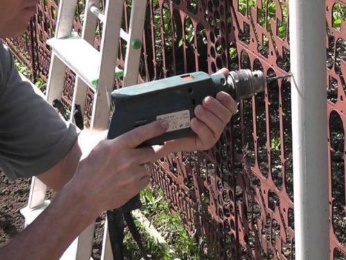 Сверление вертикальной стальной стойки шпалеры для натягивания горизонтальных рядов проволоки