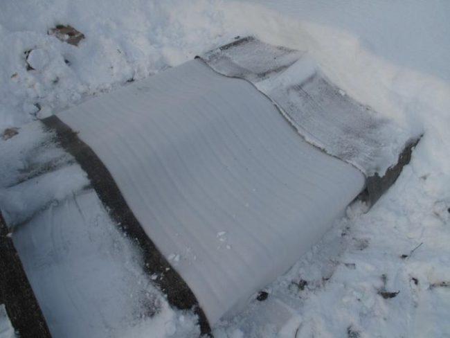 Укрытие виноградной лозы на зиму рубероидом на каркасе и белый снег вокруг