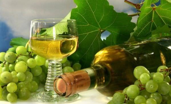 Стеклянный бокал столового вина и грозди технического сорта винограда