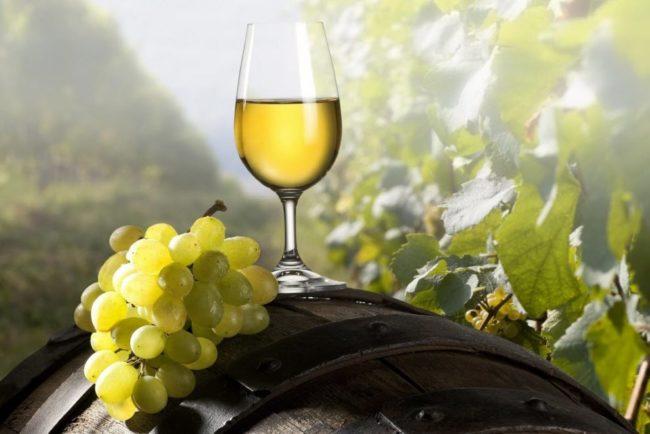 Гроздь спелого винограда сорта Макси Белый на бочке и стеклянный фужер