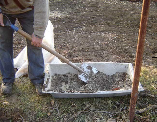 Старое оцинкованное корыто с грунтом и виноградарь с лопатой