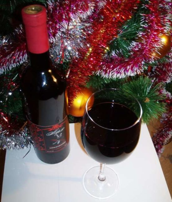 Бутылка столового вина Мерло и фужер на фоне новогодней елки