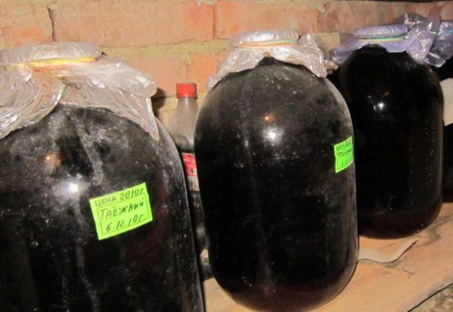 Трехлитровые стеклянные банки с виноградном соком на полке в подвальном помещении