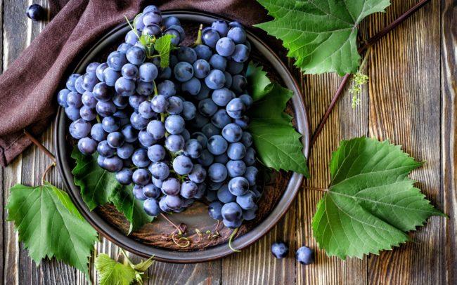 Ветви синего винограда в тарелке с листьями на деревянном столе