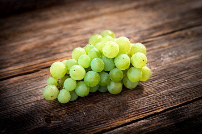 Гроздь зеленого винограда лежит на деревянном столе
