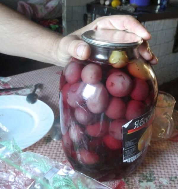 Стеклянная трехлитровая банка с крупными ягодами винограда на кухонном столе