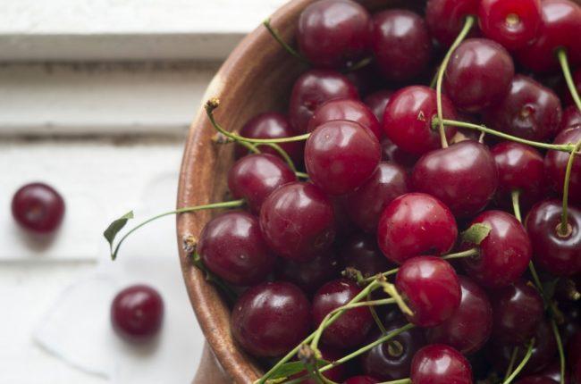 Ягоды черешни сорта Ипуть с плодоножками в чашке на столе