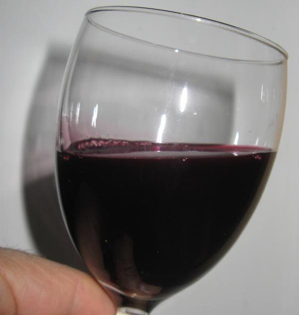 Стеклянный фужер с темным виноградным соком, по вкусу напоминающим вишневый напиток
