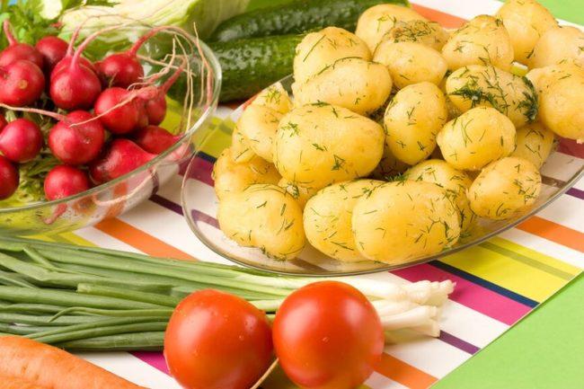 Отварная картошка в стеклянной чашке на обеденном столе и другие овощи