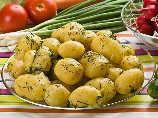 Отварной картофель с зеленью в стеклянной тарелке на обеденном столе