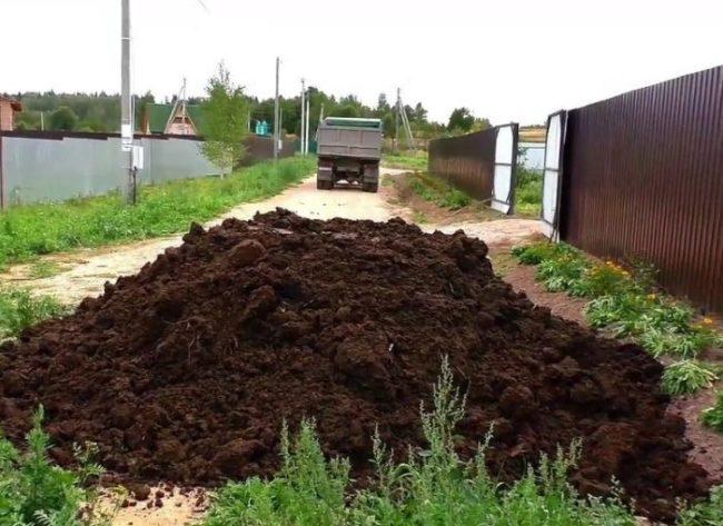 Куча перегноя для удобрения посадок помидоров в теплице частного хозяйства