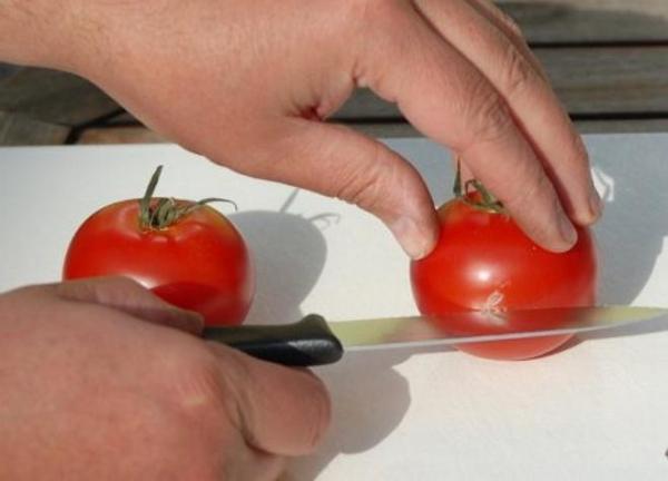 Разрезание плода томата для сбора семян в домашних условиях