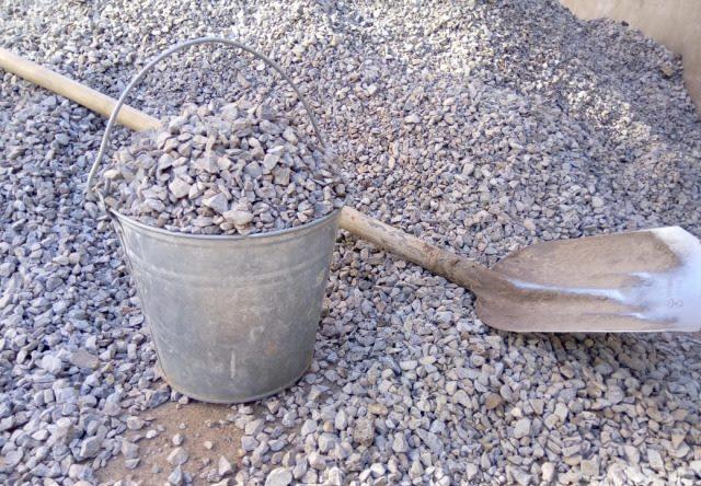 Старое ведро с щебнем для устройства дренажа в посадочной яме