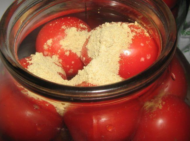 Стеклянная банка с красными помидорами и сухой горчицей
