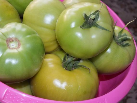 Плоды томата с плодоножкой в розовой пластиковой чашке