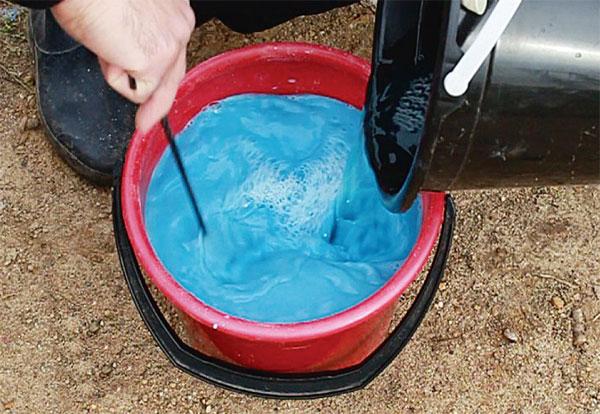 Разведение бордоской смеси в пластиковом ведре красного цвета