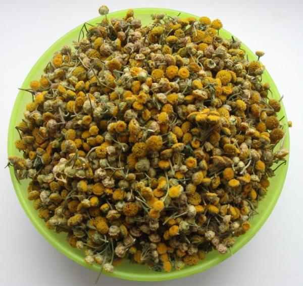 Фарфоровая чашка с желтенькими цветками пижмы для обработки яблони от вредителей