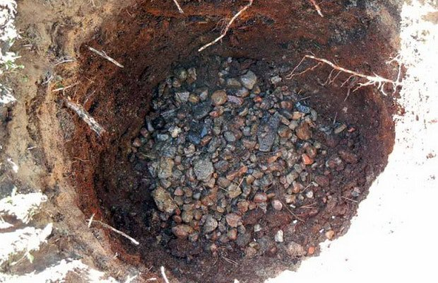 Дренаж из камня на дне посадочной ямы для саженца сливы