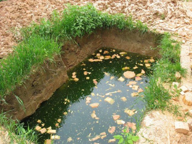 Прямоугольная яма с грунтовой водой на участке с глинистой почвой