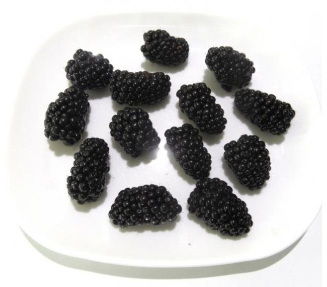 Чёрные перезревшие ягоды садовой ежевики продолговатой формы в белой тарелке