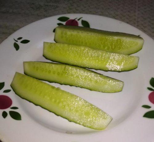 Разрезанные плоды огурца сорта Меренга F1 на фарфоровой тарелке