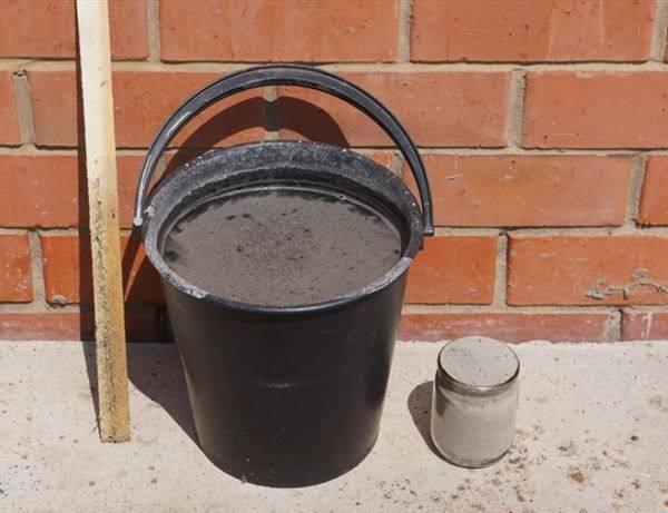 Черное пластиковое ведро с раствором древесной золы для подкормки огородных культур