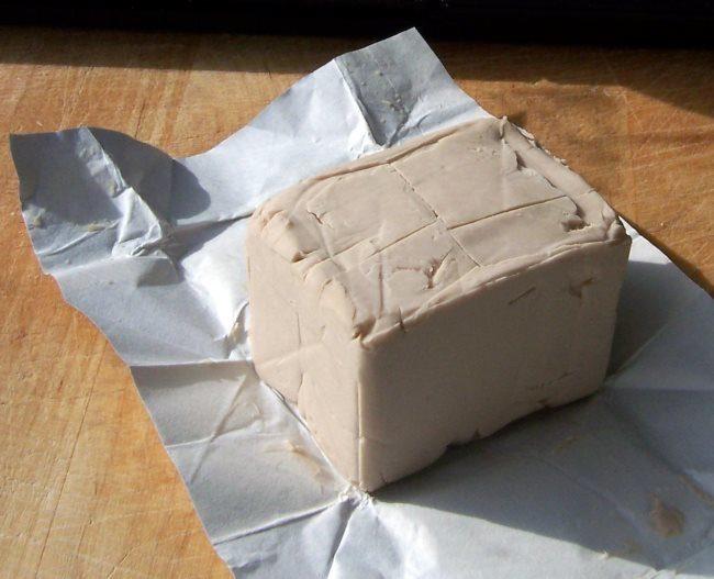 Кусочек свежих дрожжей на фольгированной бумажной упаковке