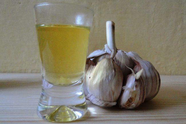 Стеклянный стакан с настоем чеснока для обработки петунии от тли
