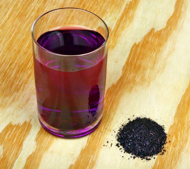 Стеклянный стакан с темным раствором перманганата калия для дезинфекции почвы