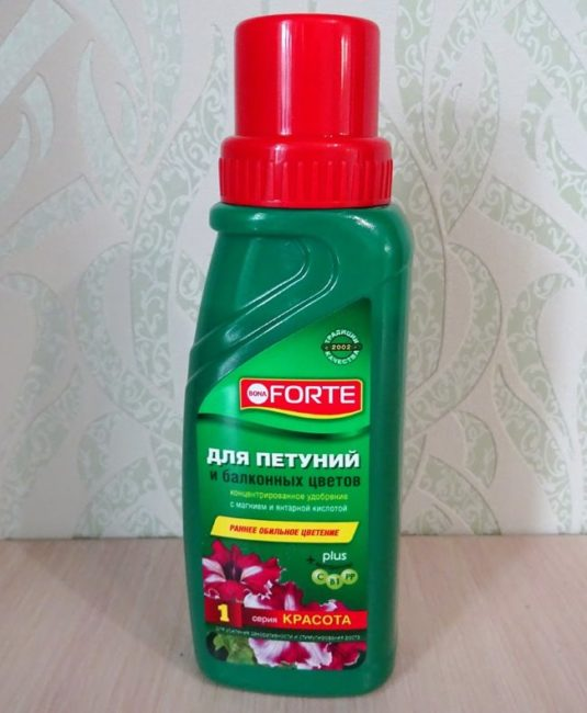 Красный колпачок на зеленом флаконе с жидкой подкормкой для петуний