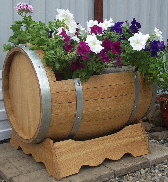Цветущая петуния в вазоне из деревянной бочки с обручами