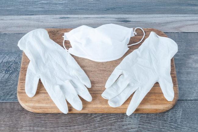 Белые перчатки на разделочной доске для защиты рук от ожога острого перца
