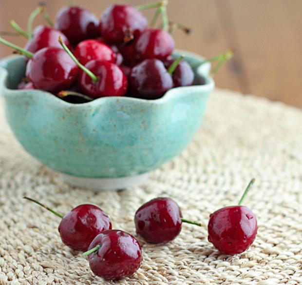 Спелые темно-красные вишни на тканевой кружевной салфетке