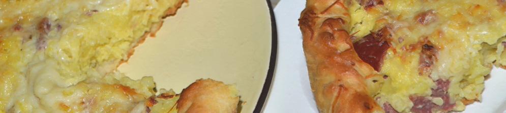 Открытый дрожжевой пирог с начинкой из картошки с колбасой разрезанный на порцию