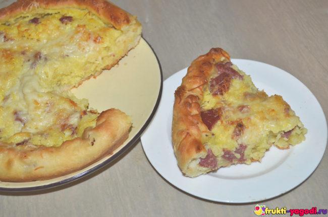 Отрезанный кусок дрожжевого пирога с картошкой и колбасой