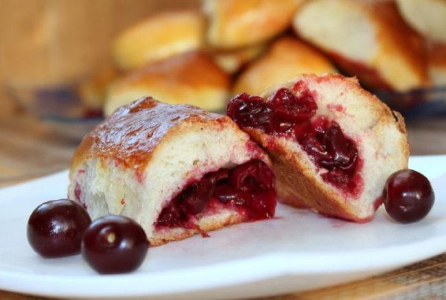 Вкусные пирожки из замороженной вишни на белой тарелке