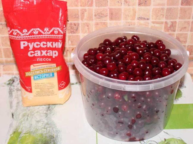Пакет сахара и емкость с мытой вишней на кухонном столе