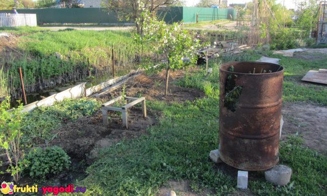 Дача в весенний период с бочкой под огонь для приготовления золы