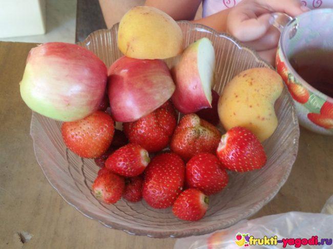 Клубника и яблоки. абрикосы на блюдце на столе